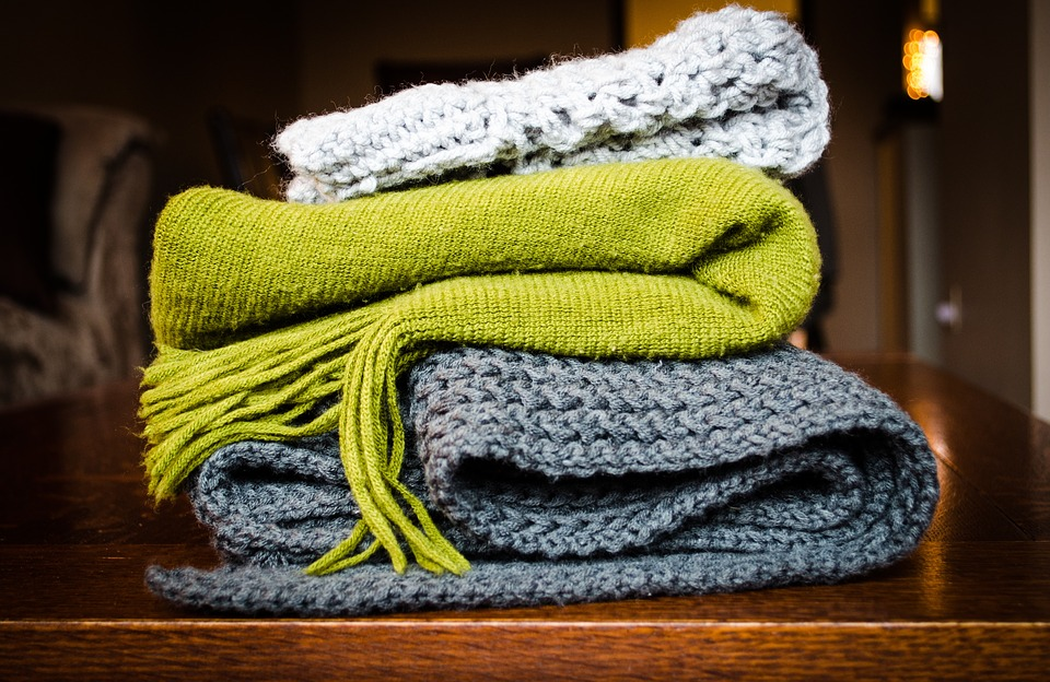 A selection of knitted blankets in light grey, green and dark grey