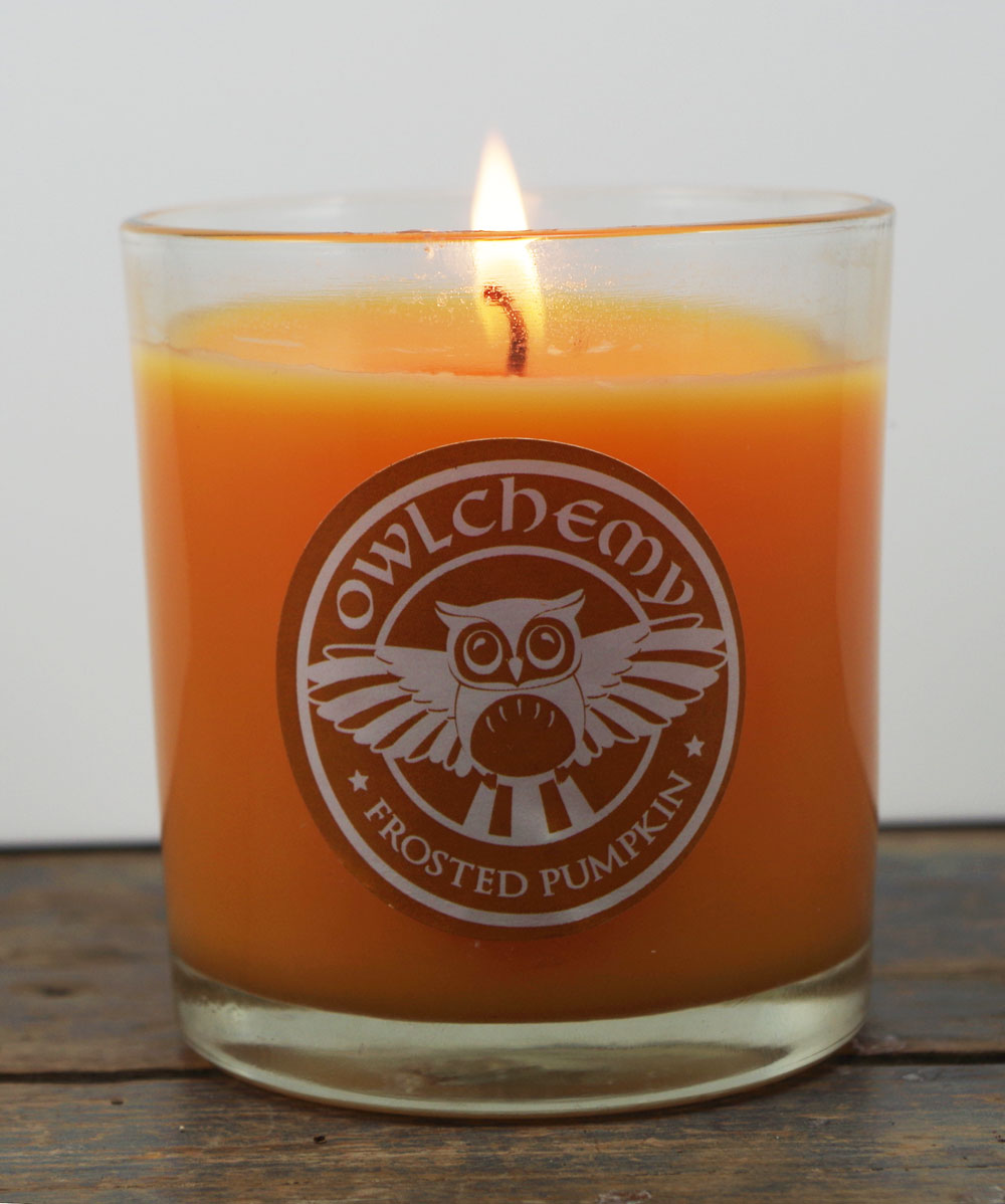 An orange Spiced Pumpkin candle with a lit flame