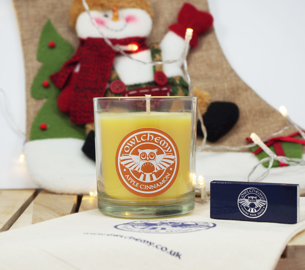 Our Apple Cinnamon candle in front of a stocking with a set of matches