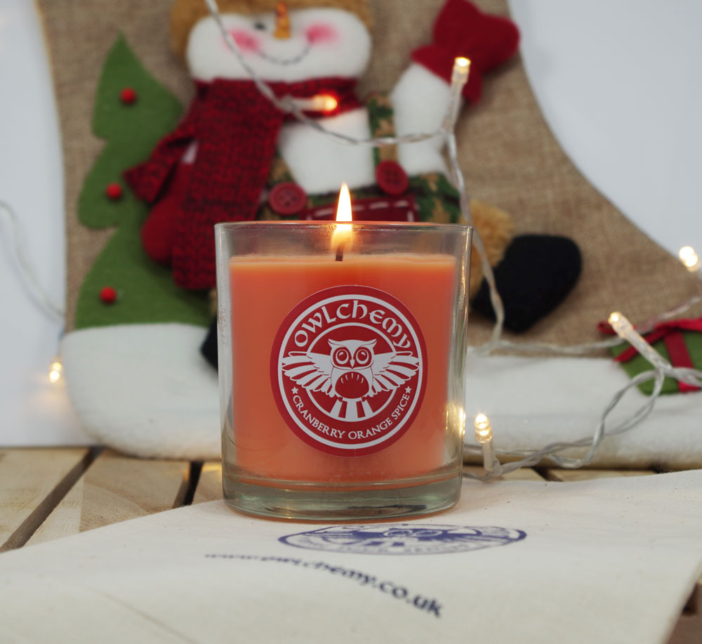 A Cranberry Orange Spice candle in front of a Christmas stocking