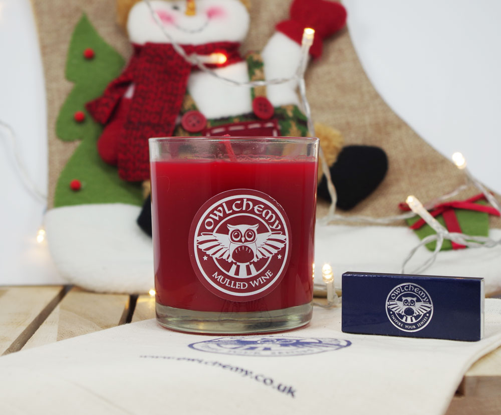 A Mulled Wine candle in front of a Christmas stocking alongside some a box of matches