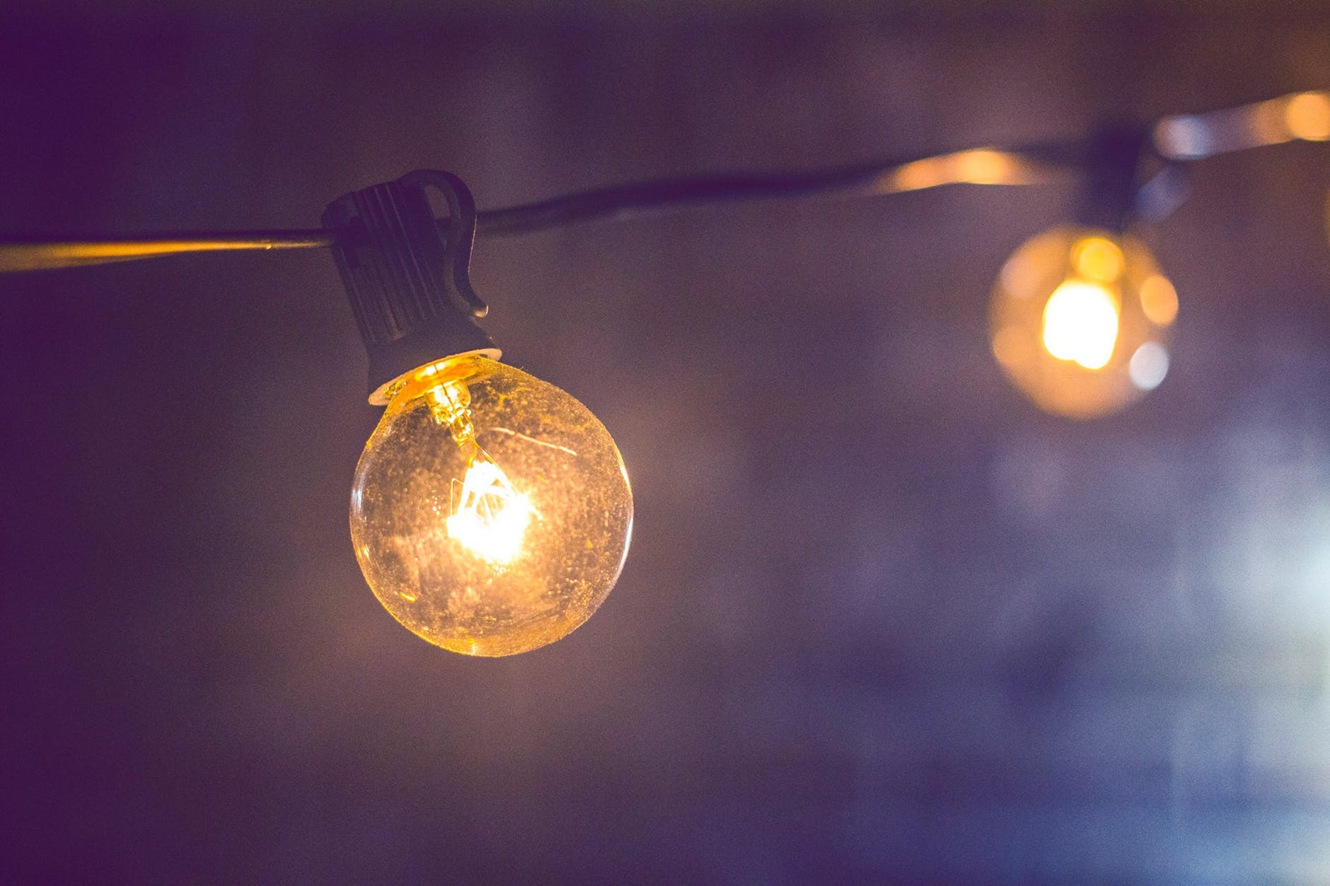 Fairy lights with big bulbs hung across a room