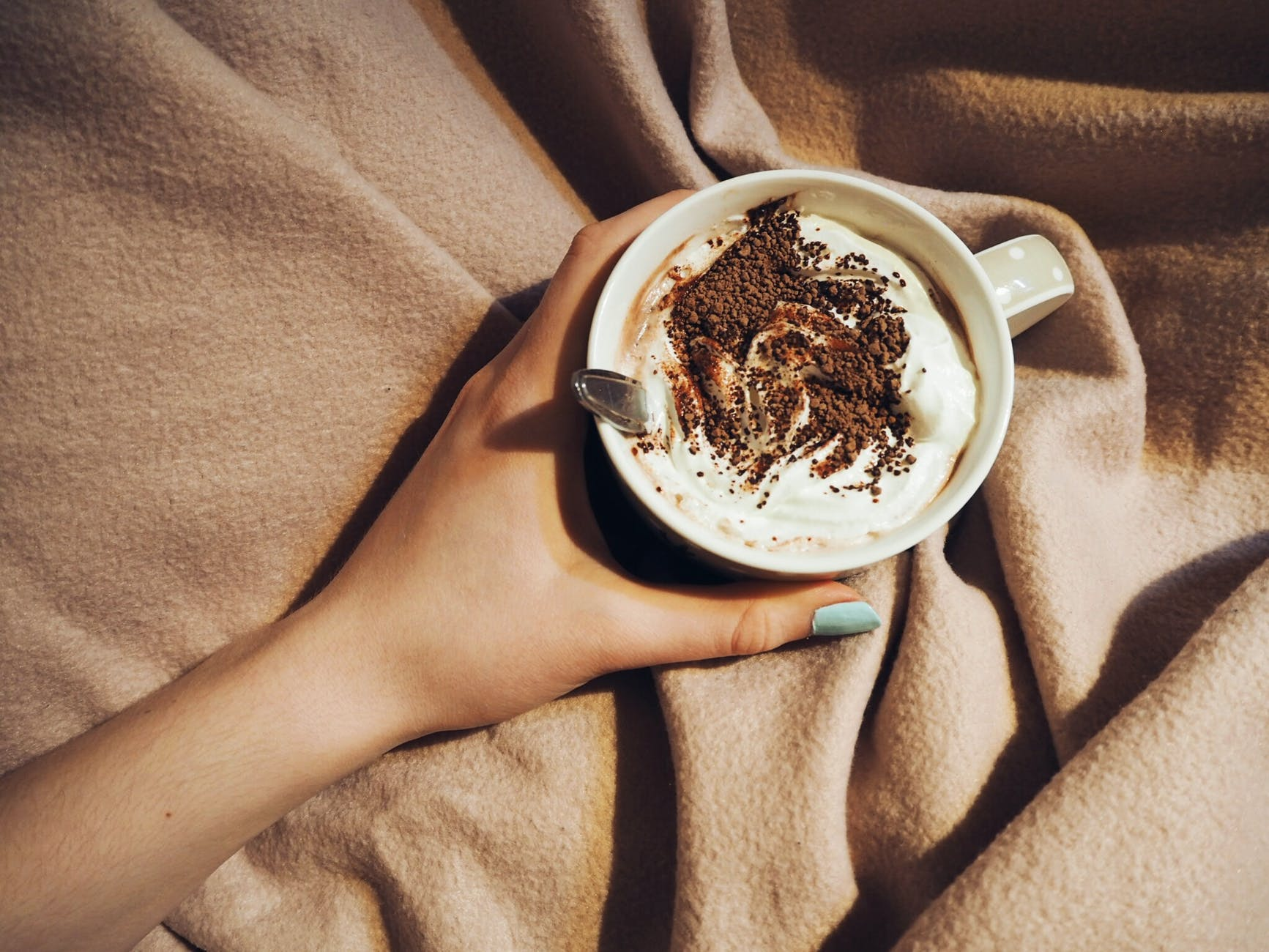 A person tucked up under a blanket holding a hot chocolate
