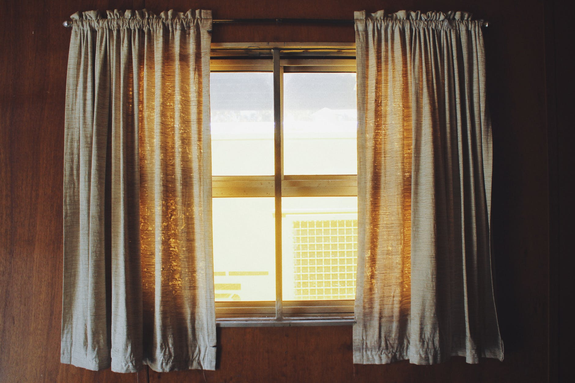 A pair of thin grey curtains hung up near a square window