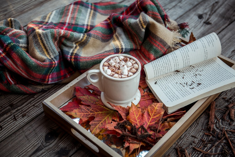 A blanket, hot drinks and book on a tray filled with autumn leaves