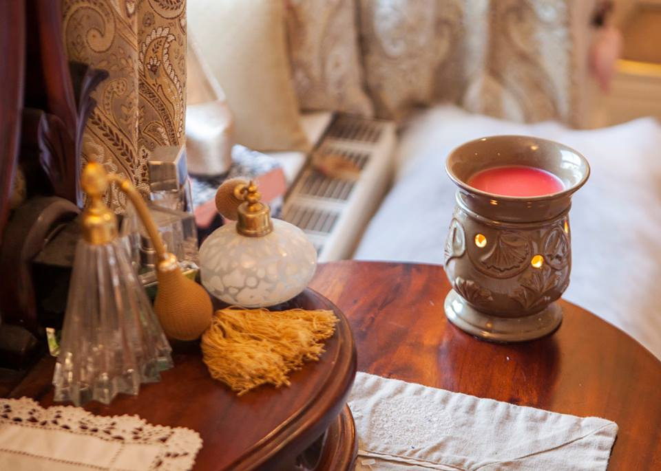 Our Morning Glory Wax Warmer lit on a wooden dressing table next to some perfume