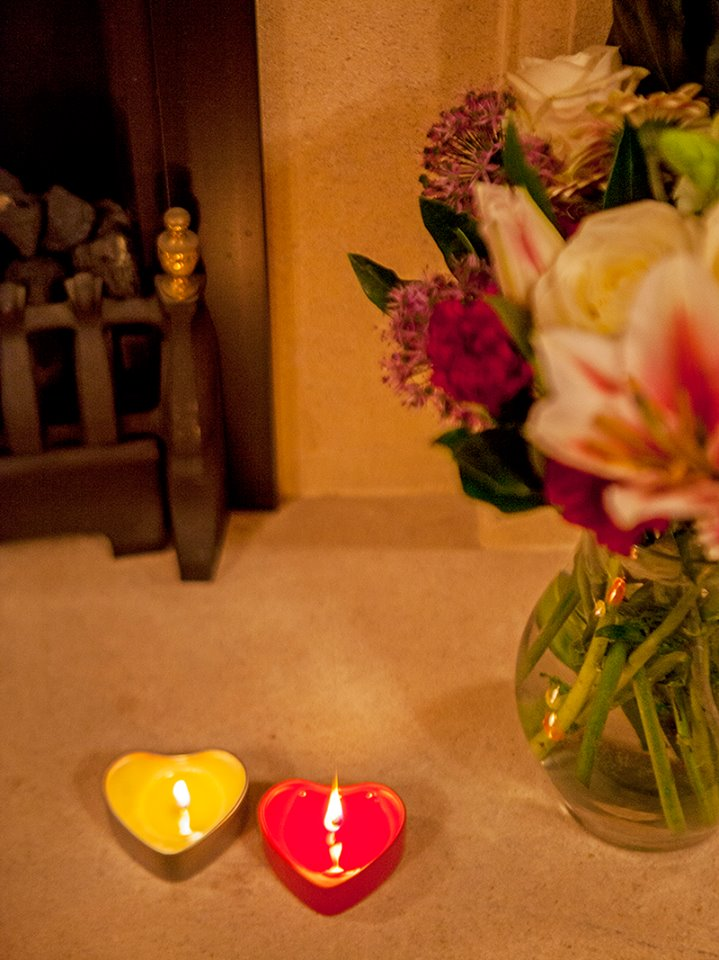 Two of our heart-shaped candles placed next to a vase of flowers