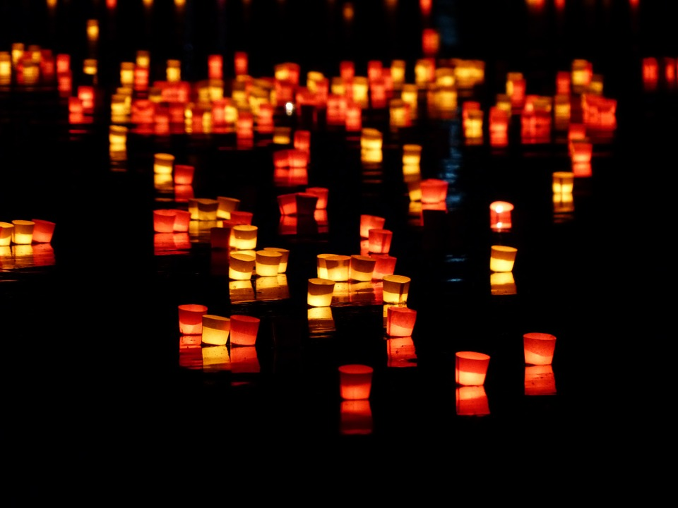 Little red, orange and yellow candles floating on a river
