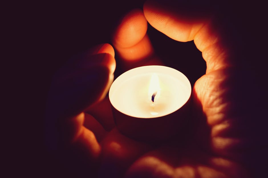 A person holding a small lit tealight in their hand and watching it glow