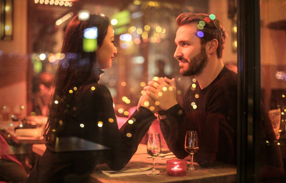 A couple enjoying a date by candle light in a restaurant