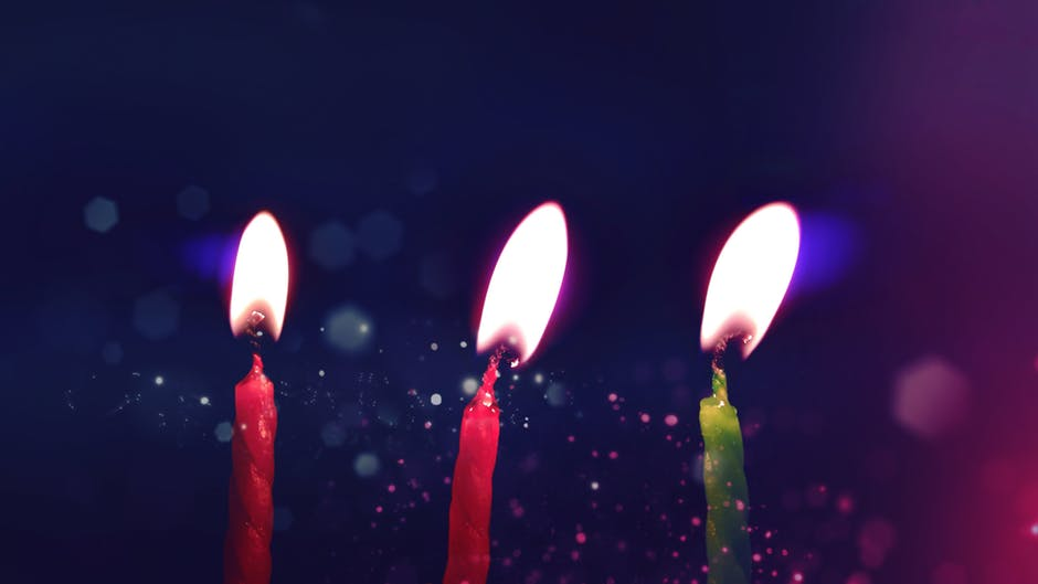 Two red candles and a green candle lit to celebrate someone's birthday