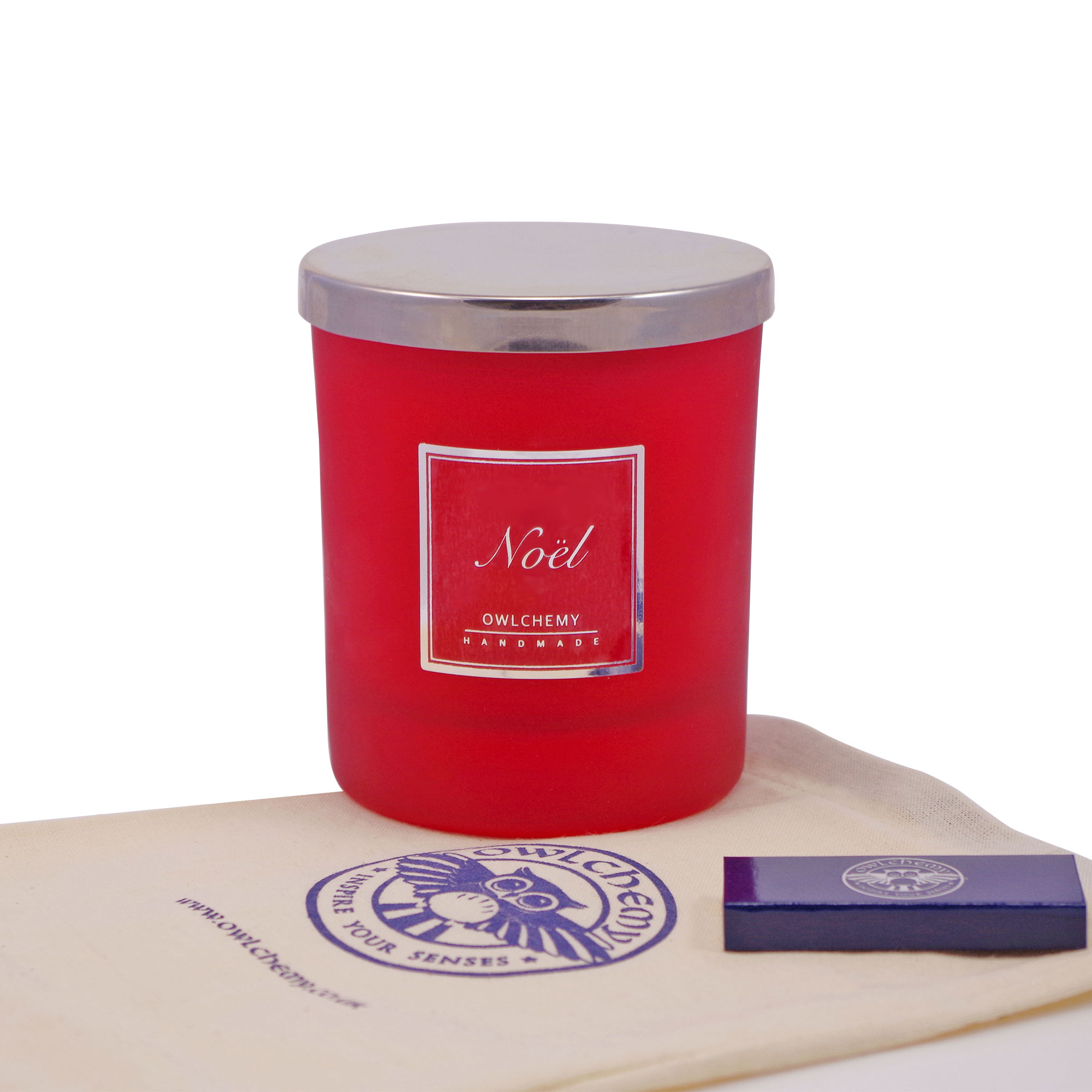 Our 250g Noel Luxury Candle placed on top of a bag with accompanying matches.