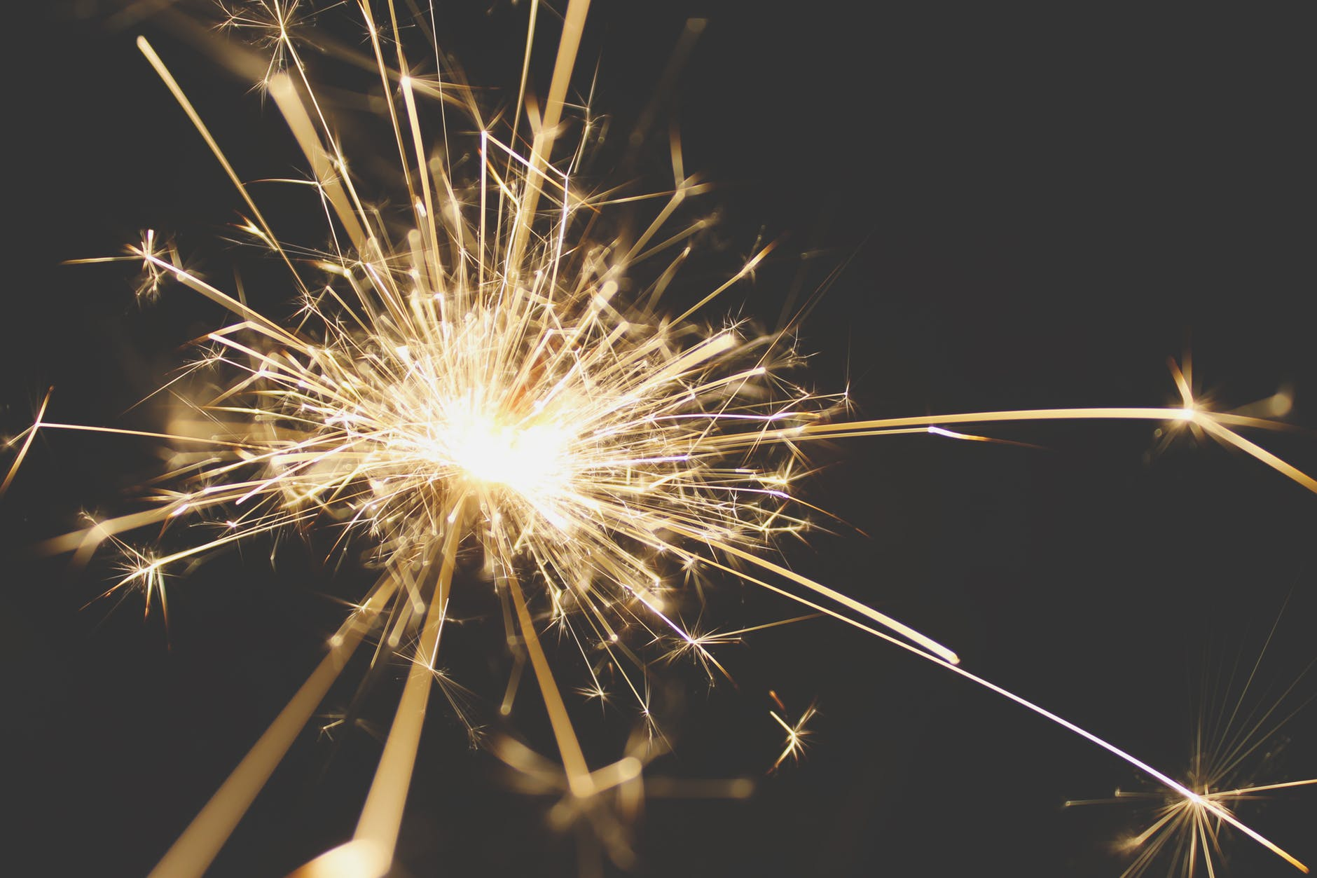 A golden sparkler glowing and streaming in the night air
