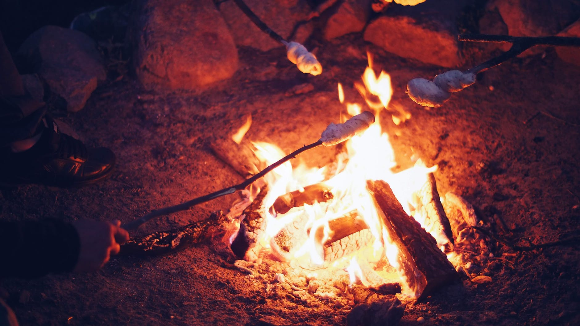 People toasting marshmallows on sticks over an open fire