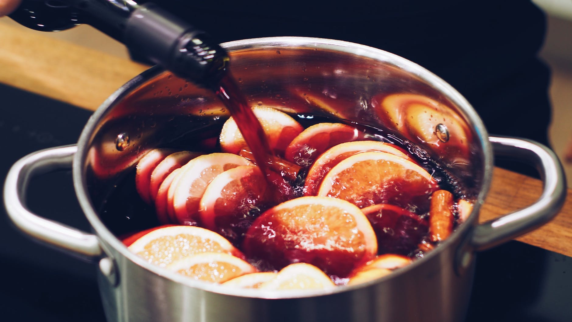 Red wine being poured into a saucepan filled with citrus fruit