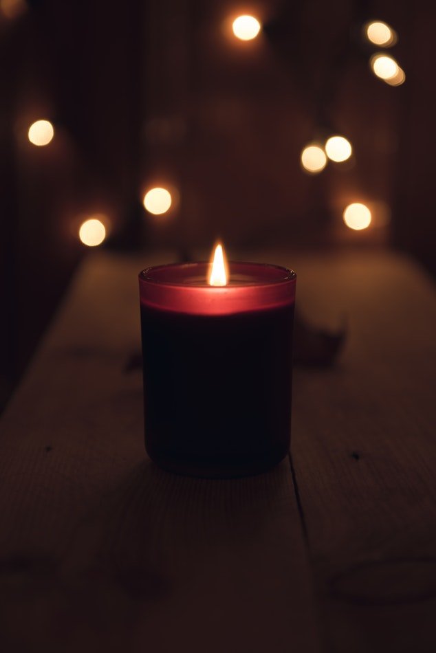 A lit red candle placed on a table in front of some white glowing fairy lights.