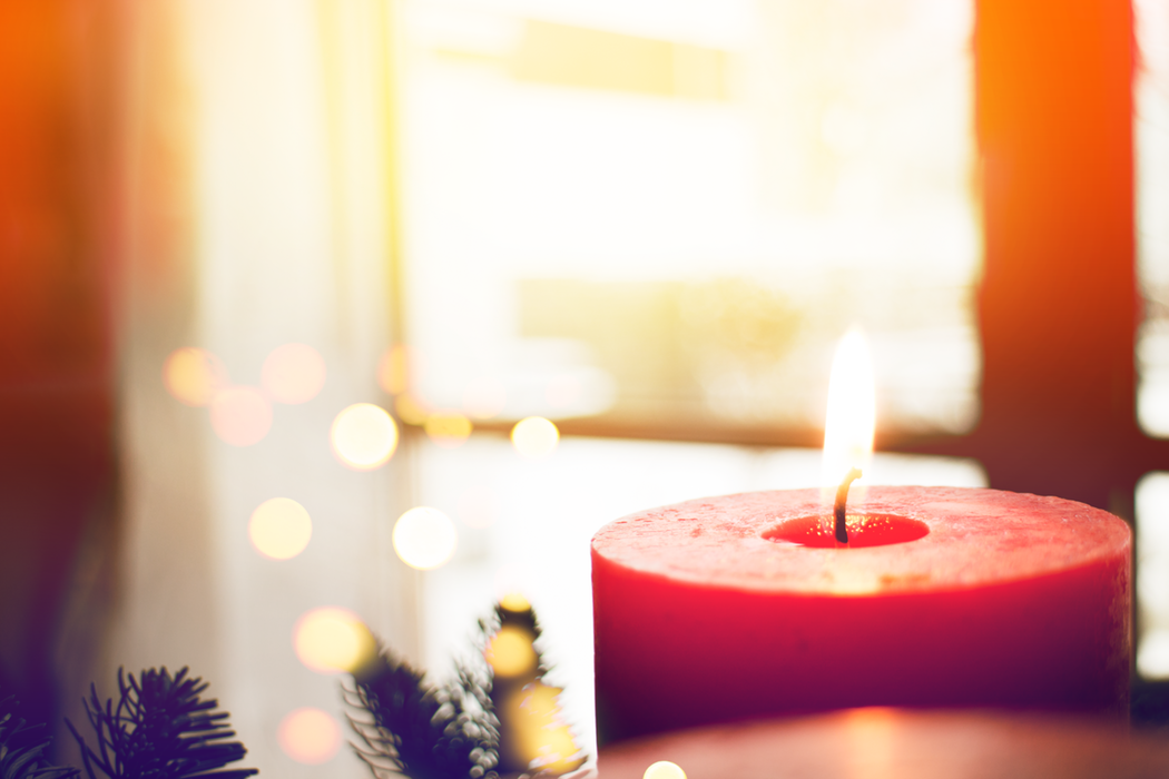 A red candle burning in front of the branches of a Christmas tree.