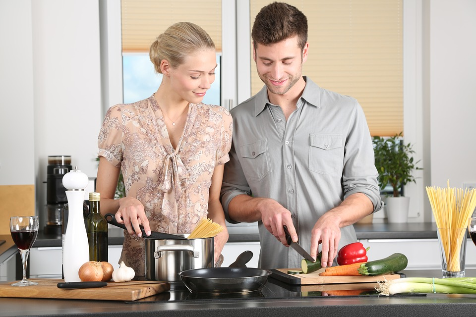 A woman and man preparing food together at a cookery class.