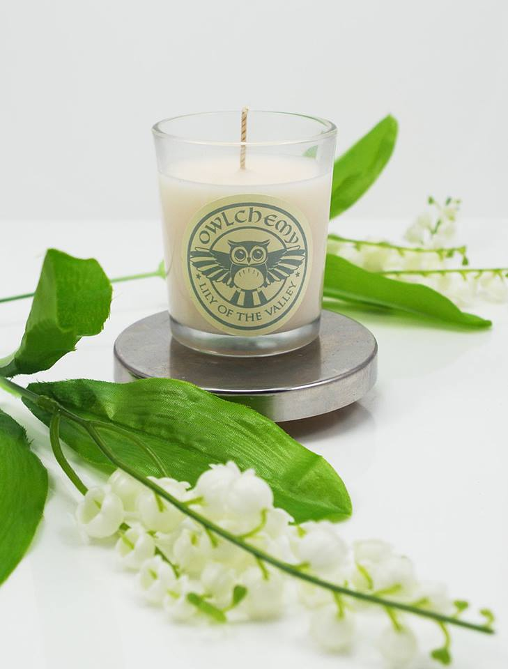 Our Lily of the Valley luxury scented candle surrounded by flowers.