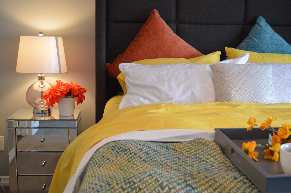 A bed with pink, yellow and blue bedding next to a bedside table with flowers.
