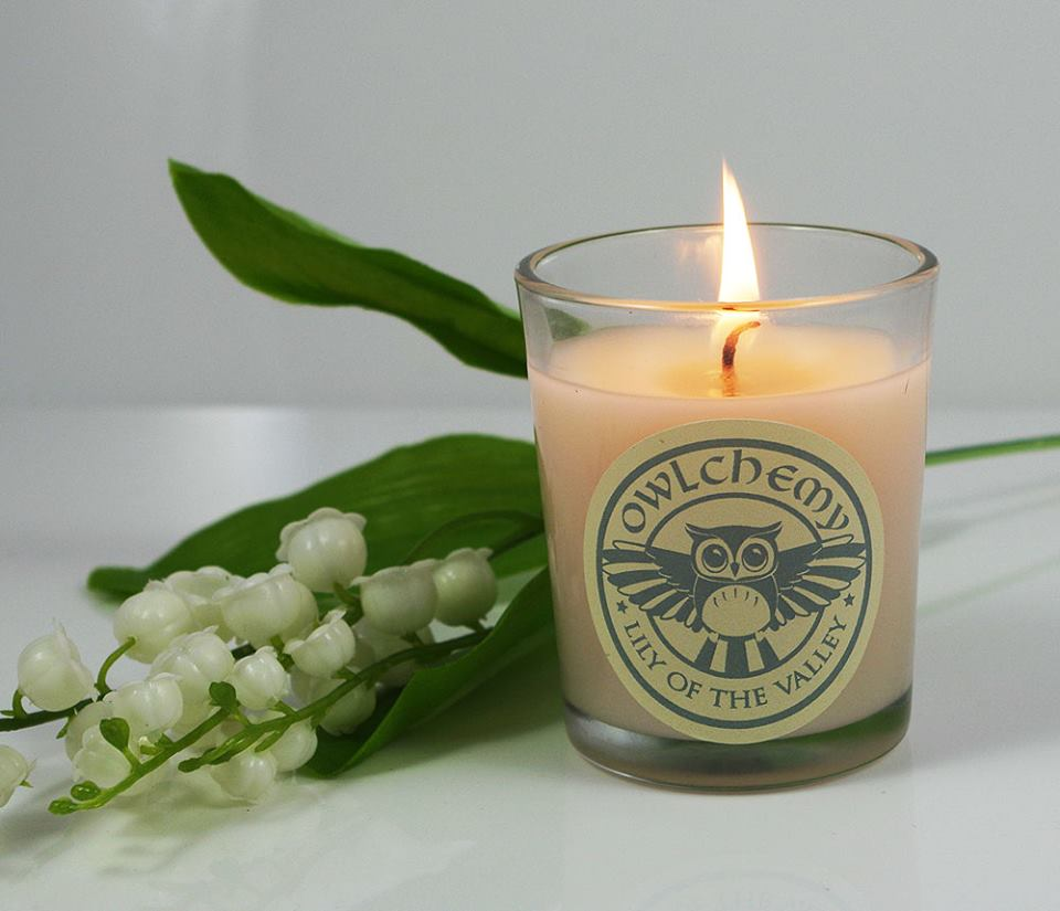 Our luxury Lily of the Valley scented candle next to a white flower.