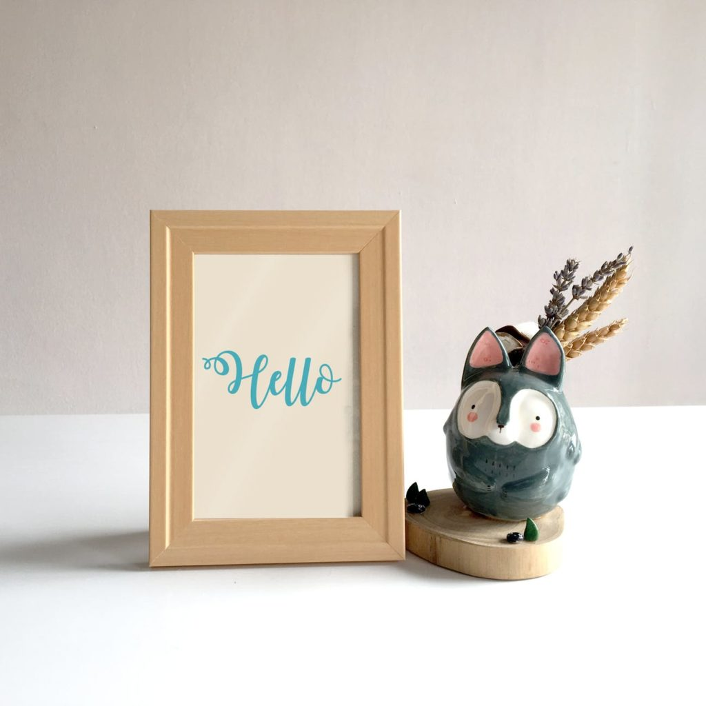A wooden photo frame next to a china ornament of a bush baby.