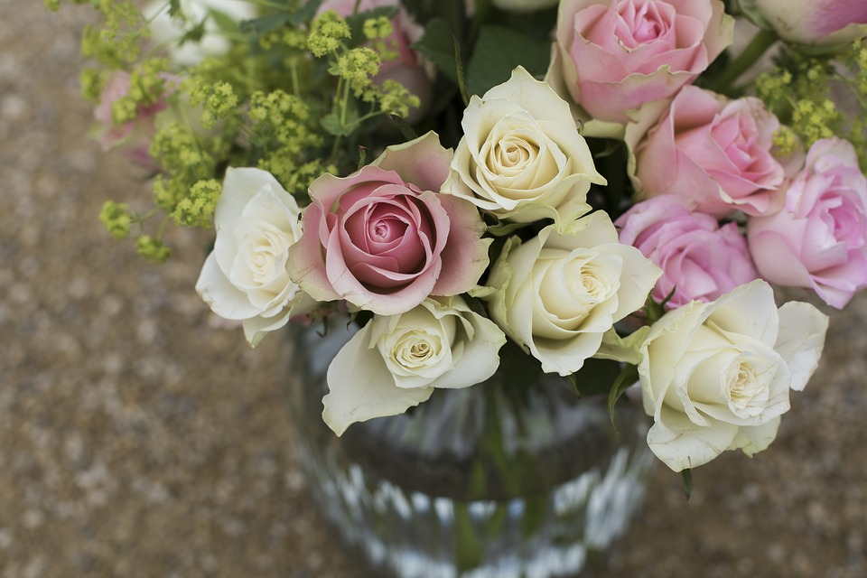 A glass vase filled with cream and pink roses as well as other foliage.