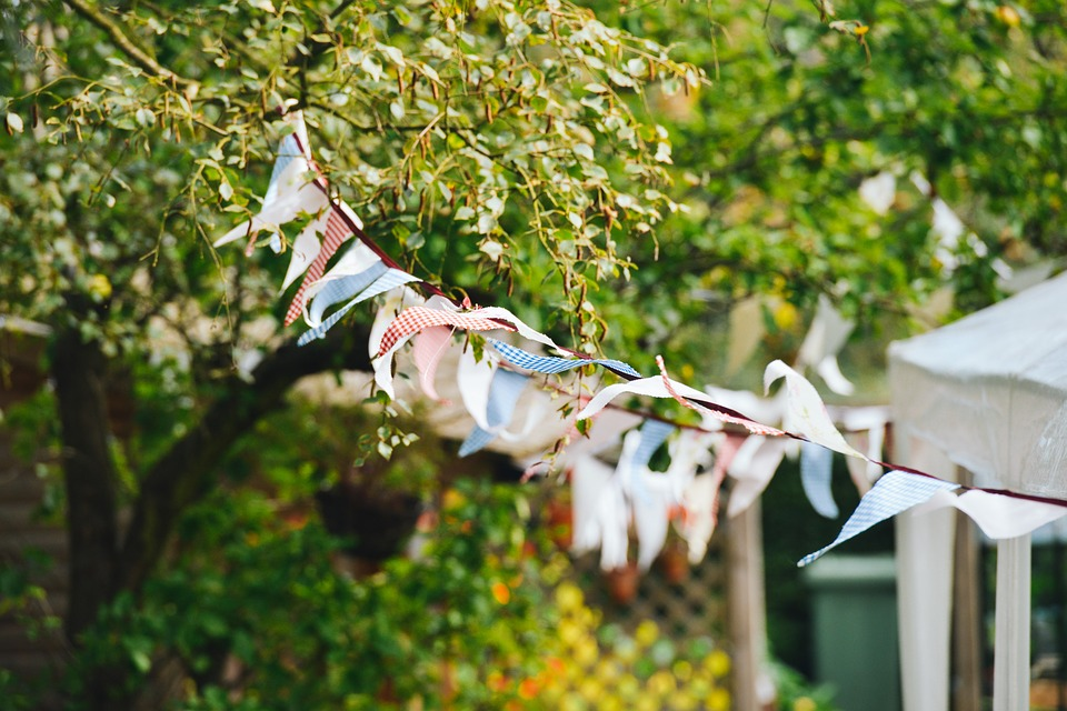 Some multicoloured patchwork bunting hung in a garden blowing in the wind.