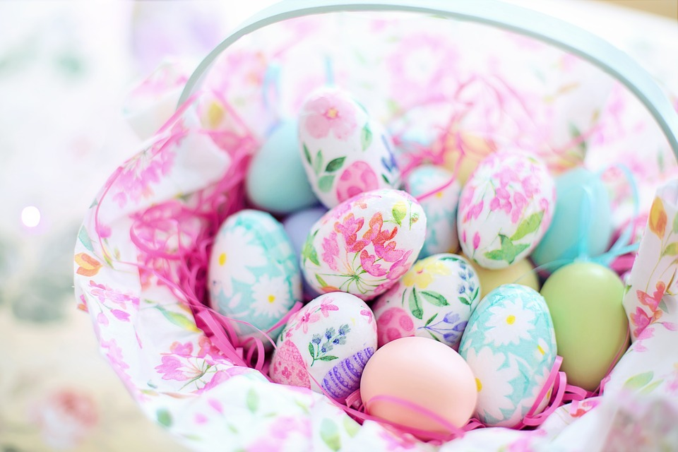 A selection of painted eggs placed in a basket lined with floral material.