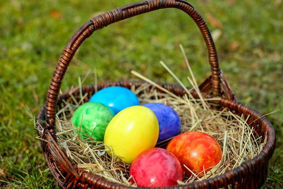 A wooden wicker basket filled with straw and selection of colourful eggs.