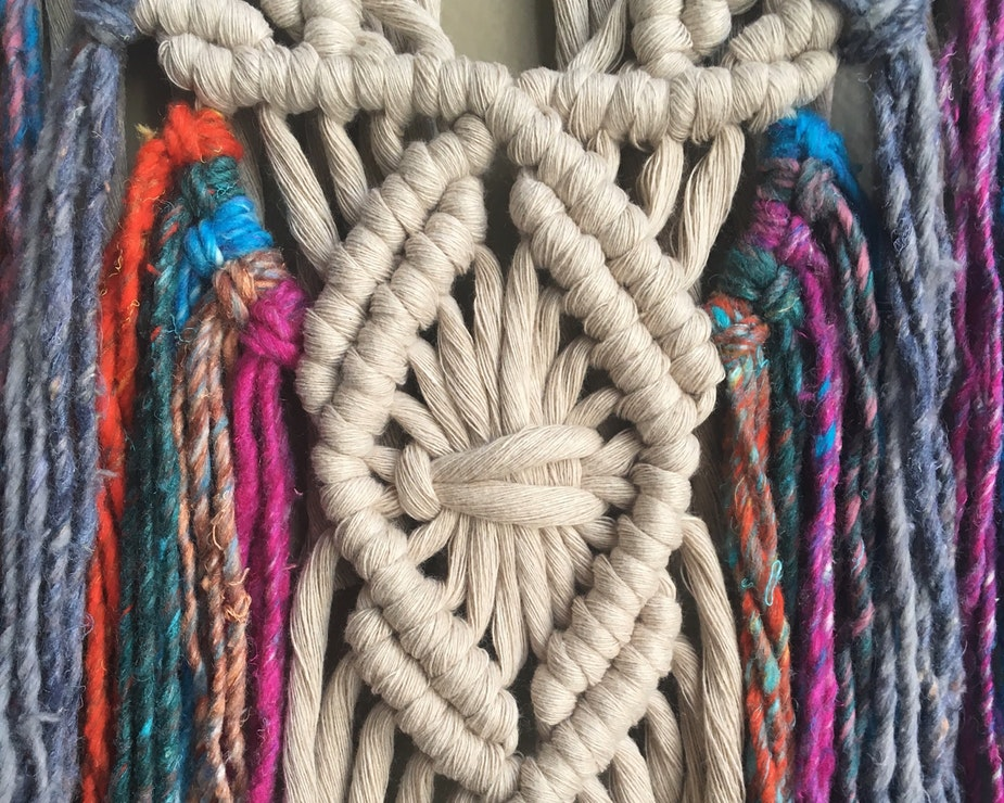 A multicoloured macramé wall hanging with a large diamond knot in the centre.